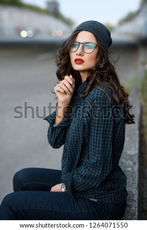 Portrait of modern curly teenage girl with red lips, standing on street