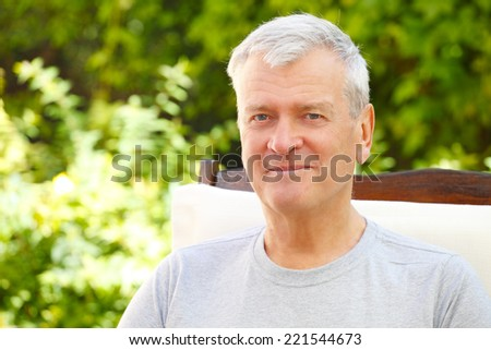 Portrait of modern grandfather sitting at garden at home.