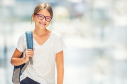 Portrait of modern happy teen school girl with bag backpack. Girl with dental braces and glasses.