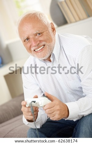 Portrait of modern senior playing computer game, smiling, looking at camera.?