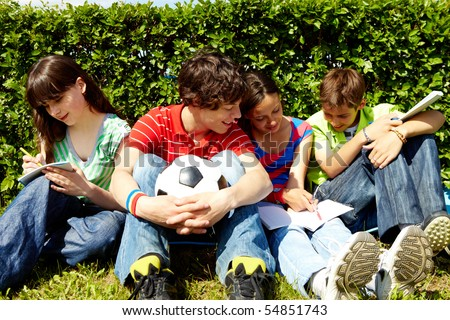 Portrait of modern teens in casual clothes sitting on green grass and writing in copybooks