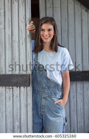 Portrait of modern young cowgirl in front of the barn #605325260