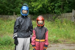 Portrait of mom and son in costumes and helmets to flying in aerodynamic tube. Entertainment in the fresh air, flying in aerodynamic tube. Outdoors activity. They are preparing to fly.