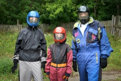 Portrait of mom, dad and son in costumes and helmets to fly in aerodynamic tube. Entertainment in the fresh air, flying in aerodynamic tube. Outdoors activity. They are preparing to fly.
