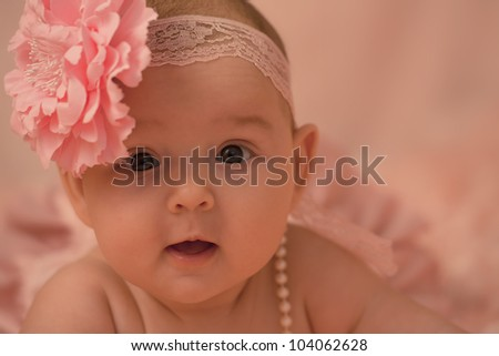 Portrait of 3 months old baby girl on pink roses background