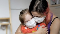 Portrait of mother and daughter in medical masks. Emotions. Happy family. Mom hugs cute little girl in protective mask. Embrace. Stay home mom. Coronavirus or COVID-19.