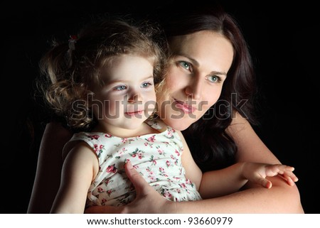 portrait of mother and daughter on a black background
