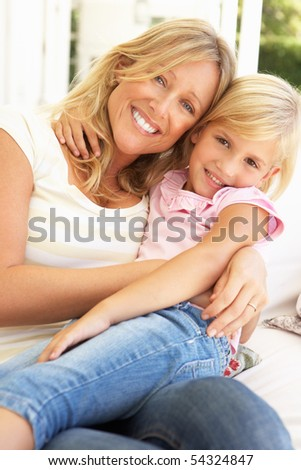Portrait Of Mother And Daughter Relaxing On Sofa