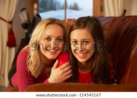 Portrait Of Mother And Daughter Relaxing On Sofa Together