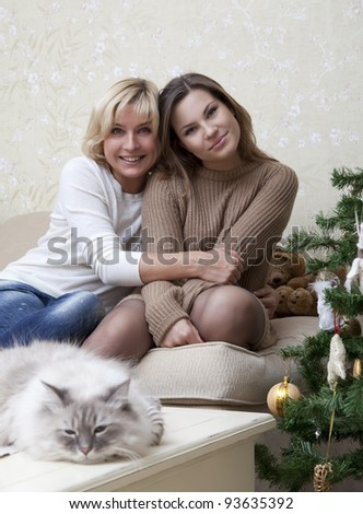 Portrait of mother and daughter with a cat