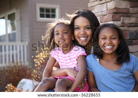 Portrait of mother and daughters sitting on porch