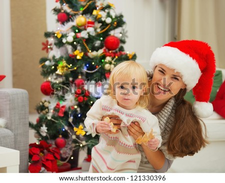 Portrait of mother and eat smeared baby near Christmas tree