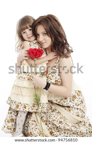 Portrait of mother and little daughter in his arms with a flower