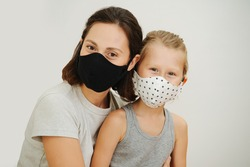 portrait of mother and son in protective masks against a white background