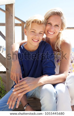 Portrait of mother and son on wooden steps by the sea, hugging looking smiling, enjoying activities outdoors. Family enjoying time together, loving closeness, travel leisure recreation lifestyle.