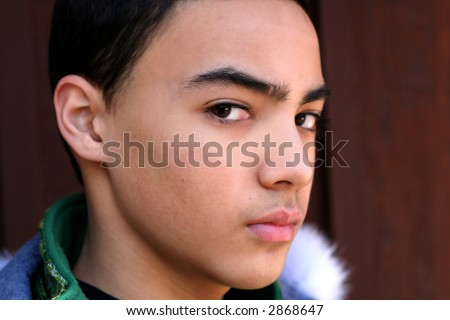 ... of multi-cultural teen boy with angry look against dark background