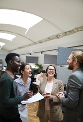 Portrait of multi -ethnic group of business people laughing happily while chatting during coffee break in office, copy space