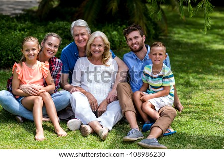 Portrait of multi generation family relaxing on grass at yard #408986230