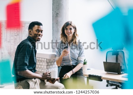 Portrait of multicultural employees dressed in formal wear dressed in formal wear smiling at camera while enjoying coffee break during working process in modern office interior behind glass wall #1244257036