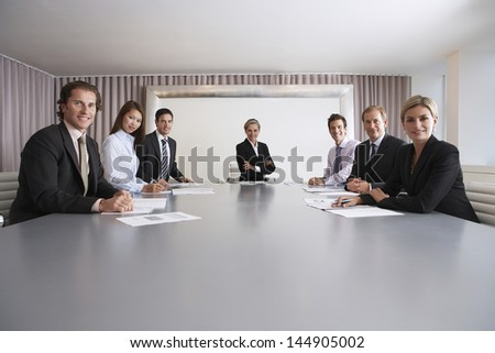 Portrait of multiethnic business people with paperwork in meeting room