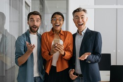 Portrait of multiracial emotional business people working in modern office. Group of overjoyed creative colleagues looking at camera. Join out team concept
