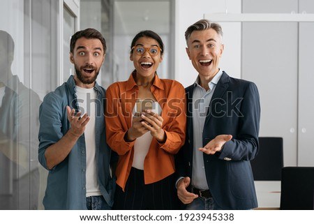 Portrait of multiracial emotional business people working in modern office. Group of overjoyed creative colleagues looking at camera. Join out team concept  Foto stock ©