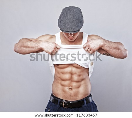 Portrait of muscle man posing in studio in hat showing his abs