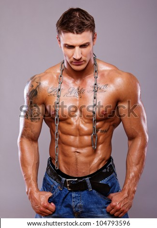 Portrait of muscle man posing in studio with chain