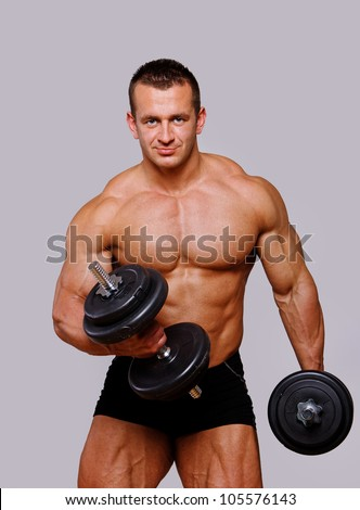 Portrait of muscle man posing in studio with dumbbells