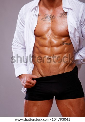 Portrait of muscle man torso on grey background