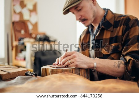 portrait of muscular middle eastern man wearing creative cup focused on work, while creating leather designs in workshop studio #644170258
