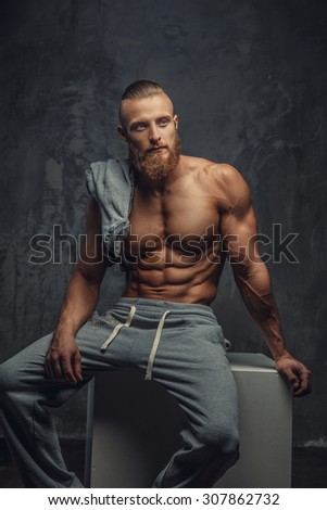 Portrait of muscular shirtless man with beard. Isolated on grey background.