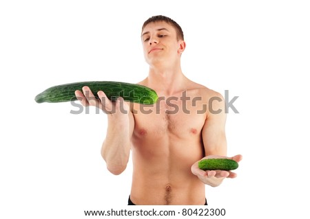 Portrait Of Muscular Young Man holding two cucumbers and choosing between them - stock photo