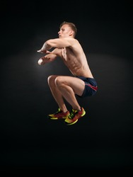 Portrait of muscular young man jumping on black background. Athlete gave jumping exercise. Studio shots in the dark tone.