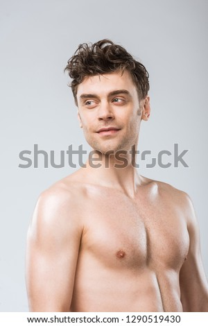 portrait of muscular young sexy man isolated on grey