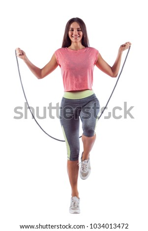 Stock Photo Portrait of muscular young woman exercising with jumping rope. Isolated on white background.