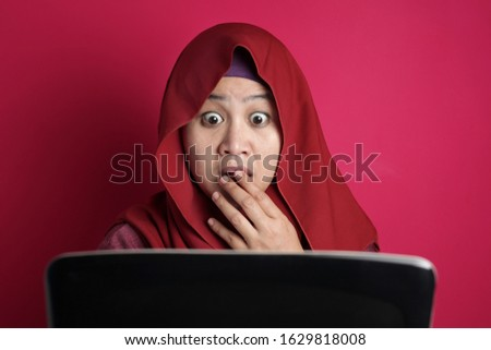 Portrait of muslim businesswoman wearing hijab shocked stunned when looking at laptop, bad negative news concept