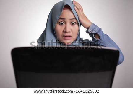 Portrait of muslim businesswoman wearing hijab using laptop with shocked stunned facial expression gesture, woman at office