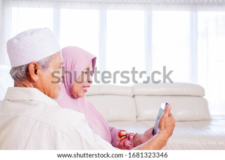 Portrait of muslim grandparents doing video call with their grandchild while sitting in living room