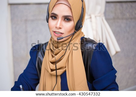 Portrait of muslim young woman customer support phone operator at workplace