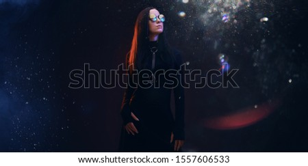 Portrait of mysterious sensual beautiful brunette woman in futuristic black dress on dark space magic background. Digital art. Augmented reality, dream, future technology, game concept. VR.