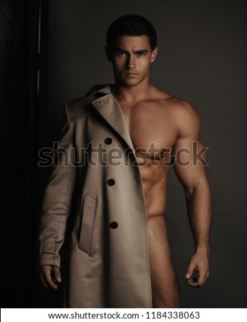 Portrait of naked muscular man covered with coat