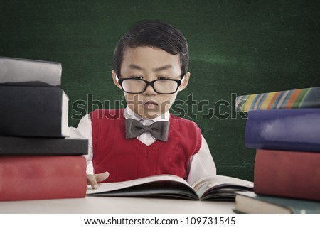 Portrait of nerd pupil reads book seriously in front of blackboard