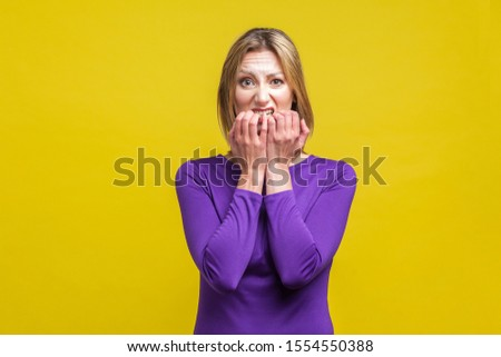 Portrait of nervous anxious woman in elegant tight purple dress biting her nails, worrying about problems, bad habit due to stress and depression. indoor studio shot isolated on yellow background
