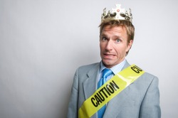 Portrait of nervous businessman with crown and sash of yellow caution tape