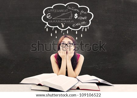 Portrait of nervous female college student with textbooks biting her nails looked thinking about her exams