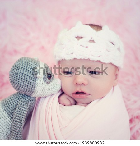 Portrait of newborn baby girl wrapped in pink wrap with knitted woolen crown headband. Infant on furry fluffy background. Curt baby with little sweet friend - knitted toy ferret Imagine de stoc ©