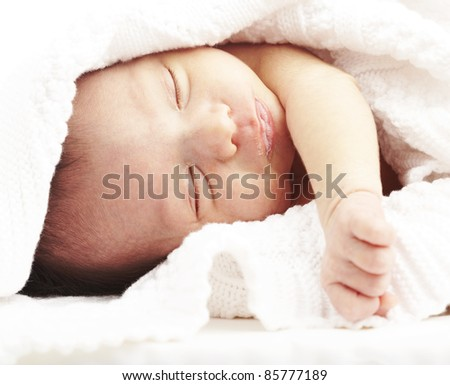 portrait of newborn baby sleeping on a bed under a towel