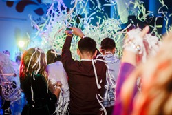 Portrait of newlywed couple and their friends at the wedding party showered with confetti in banquet hall.