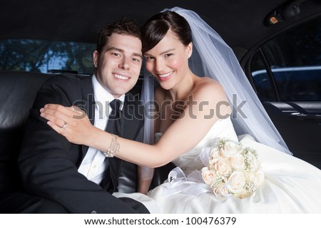 Portrait Of Newlywed Couple Smiling Sitting In Limousine.